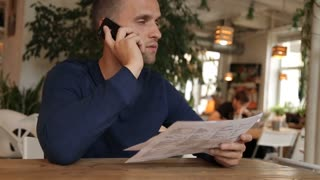 young-man-in-cafe-or-restaurant-looking-through-the-menu-talking-phone_bccqwyht_thumbnail-small01.jpg